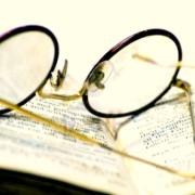 745338-un-primo-piano-di-un-vecchio-libro-aperto-con-un-paio-di-occhiali-antichi-su-di-essa1-1024x622