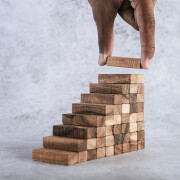 Stacking wooden blocks is at risk in creating business growth ideas.